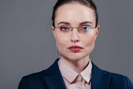 belle femme adulte en élégantes lunettes caméra isolée sur fond gris en regardant