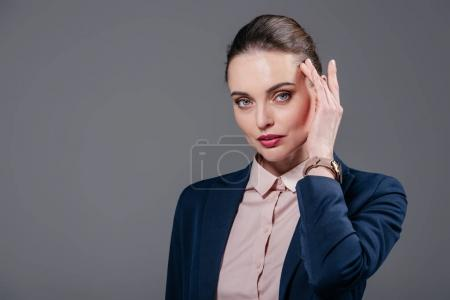 beautiful adult businesswoman in stylish suit touching her face isolated on grey