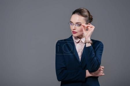 beautiful adult businesswoman in stylish suit and eyeglasses looking away isolated on grey