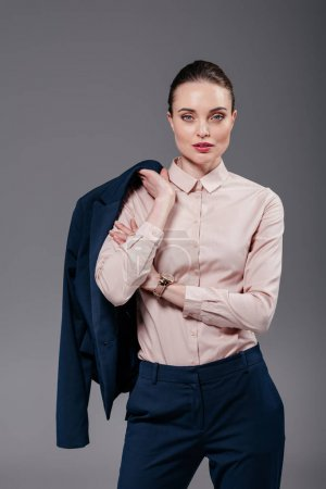 stylish adult businesswoman with jacket on shoulder looking at camera isolated on grey