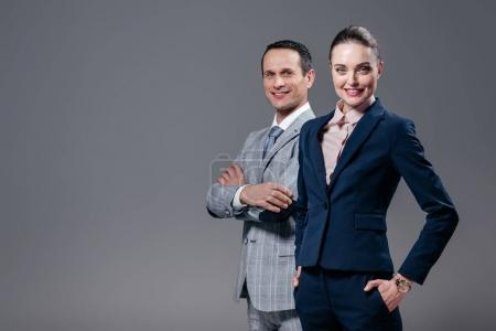 successful adult business colleagues looking at camera isolated on grey