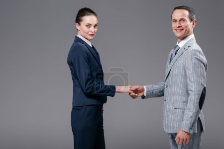 adult business colleagues shaking hands isolated on grey