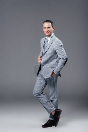 smiling adult businessman in stylish suit looking at camera on grey