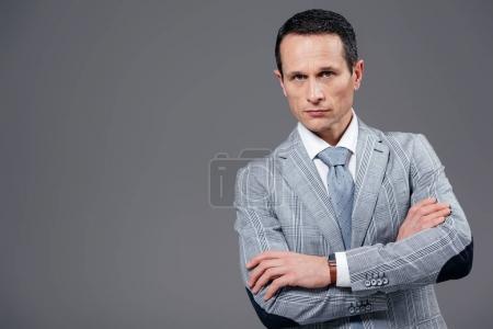 Foto de Empresario adulto guapo con los brazos cruzados mirando a cámara aislada en gris - Imagen libre de derechos