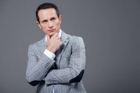 Photo pour Gentil homme d'affaires adulte avec la main sur le menton à la recherche de suite isolé sur fond gris - image libre de droit