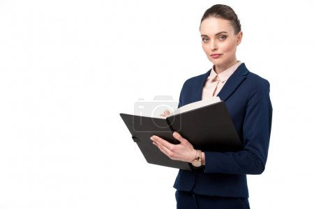 Photo for Confident adult businesswoman writing in notebook and looking at camera isolated on white - Royalty Free Image