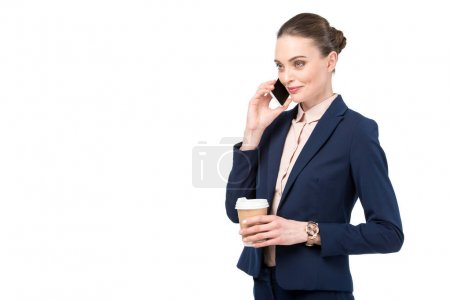adult businesswoman with coffee to go talking by phone isolated on white