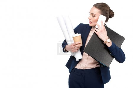 overworked adult businesswoman with lot of paperwork and coffee to go talking by phone isolated on white