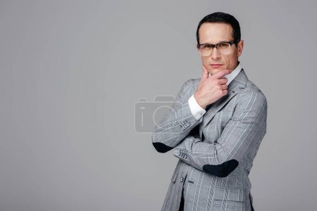 serious adult businessman with hand on chin