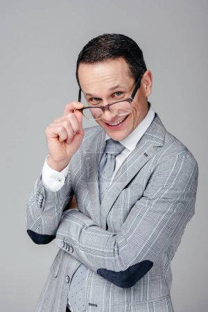 smiling adult businessman looking at camera over glasses isolated on grey