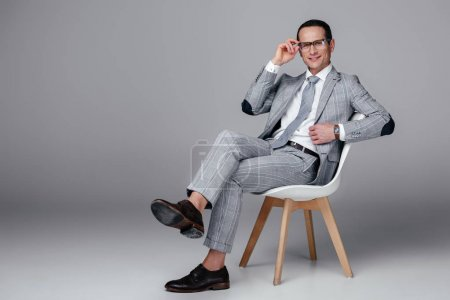 smiling adult businessman in stylish suit sitting on chair on grey