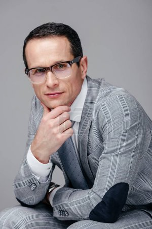 serious adult businessman with hand on chin looking at camera isolated on grey
