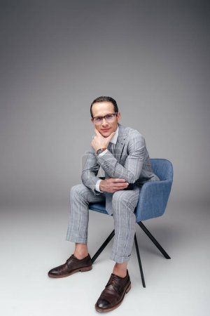 handsome adult businessman in stylish suit sitting on chair with hand on chin on grey