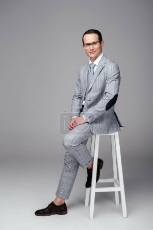 handsome adult businessman in stylish suit sitting on chair on grey
