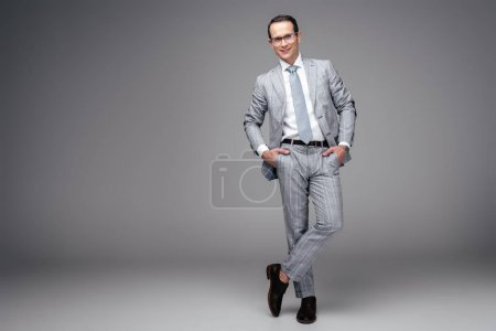 handsome adult businessman in stylish suit with hands in pockets on grey