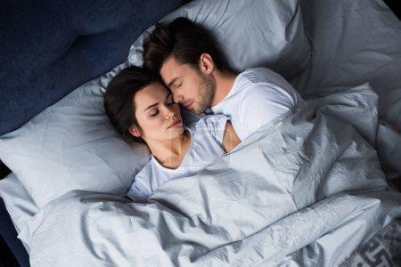 Photo pour Femme brune séduisante embrassant barbu pendant que vous dormez dans le lit - image libre de droit