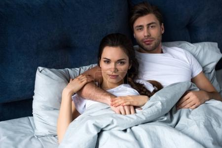 Young attractive couple hugging while lying in bed