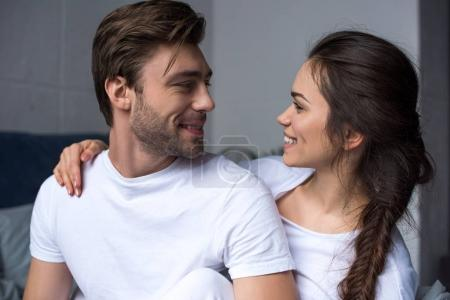 Young attractive couple hugging while sitting on bed