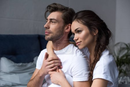Young attractive couple hugging in bedroom and looking away