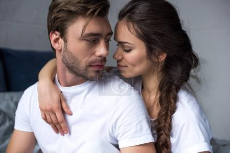 Romantic couple hugging on bed in their room