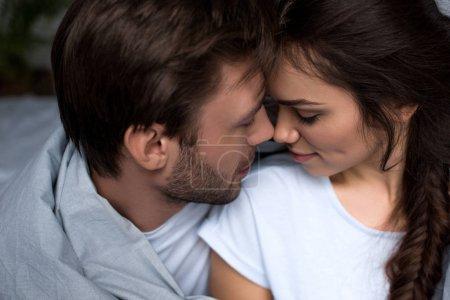 Jeune couple attrayant hugging en chambre