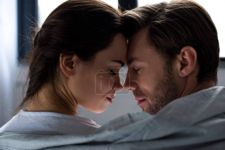 Romantic man and woman tenderly embracing in bedroom