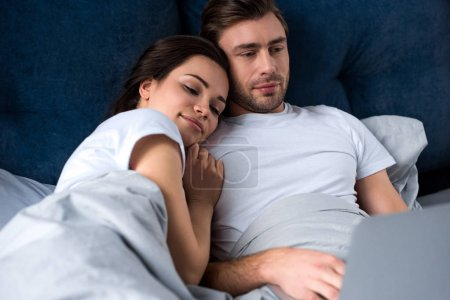 Smiling couple looking at laptop while lying in bed