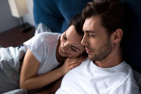 Smiling man and woman tenderly embracing while lying in bed