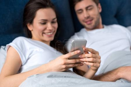 Photo for Woman using smartphone while lying in bed with her husband - Royalty Free Image