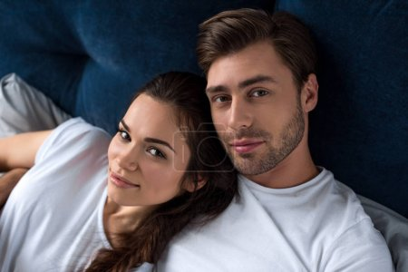 Photo for Smiling man and woman tenderly embracing in bed - Royalty Free Image