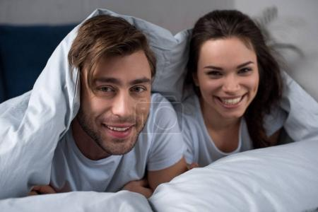 Photo for Smiling man and woman lying in bed under blanket - Royalty Free Image