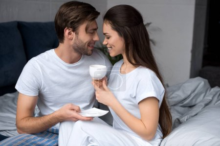 Happy couple with coffee embracing in bed