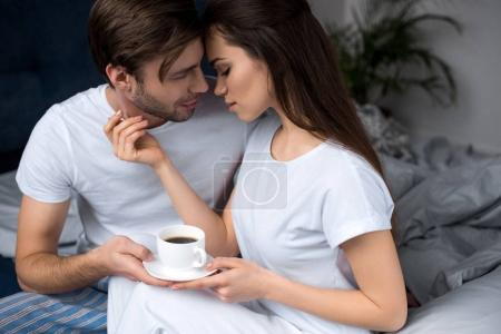 Woman holding cup of coffee and embracing her husband while in bed