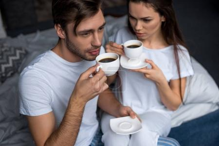 Photo for Bearded man and attractive brunette woman drinking coffee in bed - Royalty Free Image