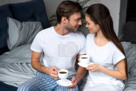 Smiling wife and husband drinking coffee in bed