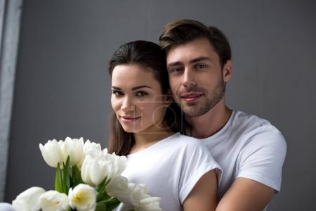 Smiling man and woman with flowers tenderly embracing in bedroom