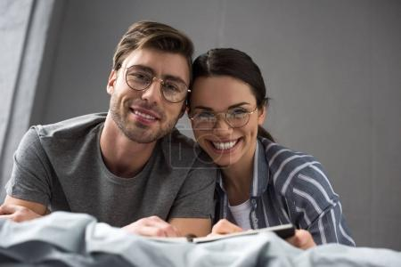 Photo for Smiling couple in glasses writing in notepad while lying in bed - Royalty Free Image