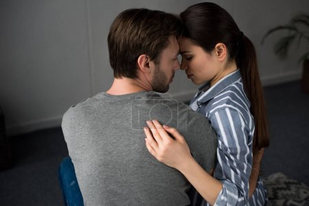 Romantic couple tenderly embracing in bedroom
