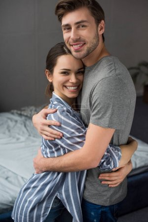 Smiling couple tenderly embracing in bedroom