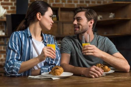 Smiling man and woman drinking juice and eating croissants by kitchen table