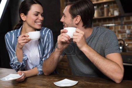Happy couple enjoying breakfast with coffee on kitchen