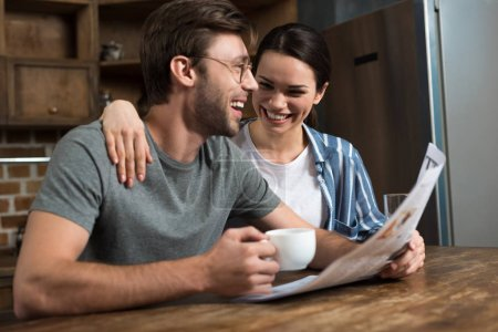 Happy couple enjoying breakfast with coffee and newspaper on kitchen