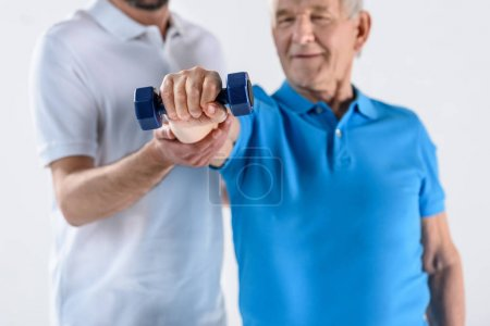 partial view of rehabilitation therapist assisting senior man exercising with dumbbell isolated on grey