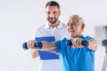 portrait of rehabilitation therapist with notepad assisting senior man exercising with dumbbells on grey backdrop