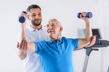 portrait of rehabilitation therapist assisting senior man exercising with dumbbells on grey backdrop