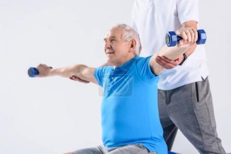 Photo for Cropped shot of rehabilitation therapist assisting senior man exercising with dumbbells on grey backdrop - Royalty Free Image