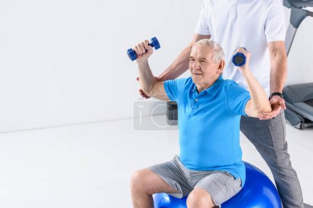partial view of rehabilitation therapist assisting senior man exercising with dumbbells on fitness ball on grey backdrop