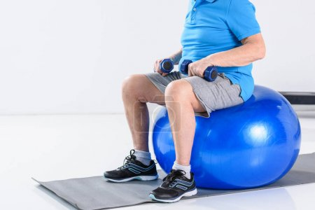 cropped shot of senior man with dumbbells sitting on fitness ball on grey backdrop