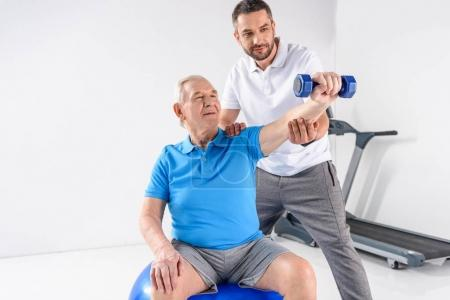 portrait of rehabilitation therapist assisting senior man exercising with dumbbell on grey backdrop