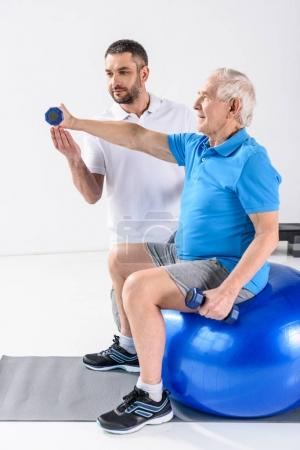 rehabilitation therapist assisting senior man exercising with dumbbells on fitness ball